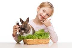 Κορίτσι με το καφετί λαγουδάκι στη χλόη και το τηλέφωνο Στοκ φωτογραφία με δικαίωμα ελεύθερης χρήσης