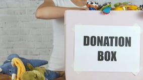 Κορίτσι με το κιβώτιο των παιχνιδιών έτοιμων για τη δωρεά απόθεμα βίντεο
