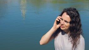 Κορίτσι με το κινητό τηλέφωνο από το νερό Μια γυναίκα μιλά στο τηλέφωνο στο ανάχωμα ποταμών μια ηλιόλουστη ημέρα απόθεμα βίντεο