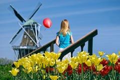 Κορίτσι με το κόκκινους μπαλόνι και τον ανεμόμυλο στοκ εικόνες με δικαίωμα ελεύθερης χρήσης