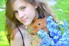 Κορίτσι με το κόκκινο κουνέλι και ανθοδέσμη με το μπλε delphinium και Στοκ Φωτογραφίες