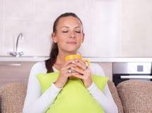 Κορίτσι με το μαξιλάρι και φλιτζάνι του καφέ στον καναπέ Στοκ εικόνες με δικαίωμα ελεύθερης χρήσης
