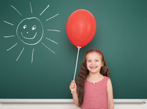 Κορίτσι με το μπαλόνι και ήλιος κοντά στο σχολικό πίνακα Στοκ Εικόνες