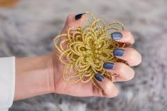 Κορίτσι με το μπλε ναυτικό μανικιούρ στα καρφιά δάχτυλων που κρατά το διακοσμητικό χρυσό λουλούδι στοκ εικόνα