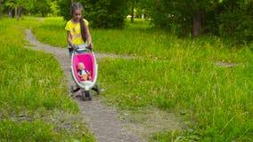 Κορίτσι με το μωρό - κούκλα στο πάρκο φιλμ μικρού μήκους