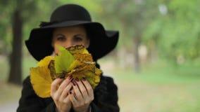 Κορίτσι με το παιχνίδι καπέλων με τα φύλλα απόθεμα βίντεο