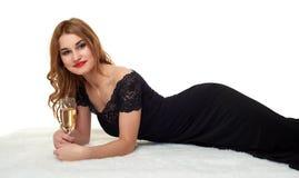 Κορίτσι με το ποτήρι της σαμπάνιας που βρίσκεται στη γούνα, που φορά ένα μαύρο φόρεμα Στοκ Εικόνα