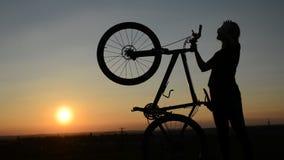 Κορίτσι με το ποδήλατο στο ηλιοβασίλεμα απόθεμα βίντεο