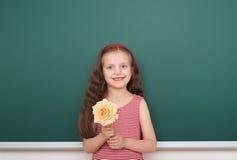 Κορίτσι με το ροδαλό λουλούδι κοντά στο σχολικό πίνακα Στοκ Εικόνες