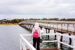 Κορίτσι με το ρόδινο σακίδιο πλάτης που διαβάζει ένα σημάδι από το νερό στοκ εικόνες