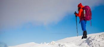 Κορίτσι με το σακίδιο πλάτης που περπατά στο χιόνι στα βουνά Στοκ Φωτογραφία