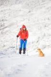 Κορίτσι με το σκυλί στα χειμερινά βουνά Στοκ Φωτογραφίες
