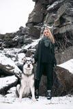 Κορίτσι με το σκυλί Malamute μεταξύ των βράχων το χειμώνα Στοκ φωτογραφίες με δικαίωμα ελεύθερης χρήσης