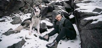 Κορίτσι με το σκυλί Malamute μεταξύ των βράχων το χειμώνα Στοκ Φωτογραφία