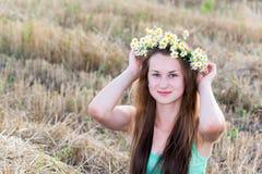 Κορίτσι με το στεφάνι των μαργαριτών σε έναν τομέα Στοκ εικόνα με δικαίωμα ελεύθερης χρήσης