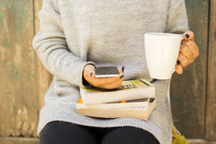Κορίτσι με το τηλέφωνο, το φλιτζάνι του καφέ και τα βιβλία κυττάρων Στοκ Εικόνα