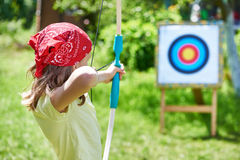 Κορίτσι με το τόξο που πυροβολεί στον αθλητικό στόχο στοκ εικόνες