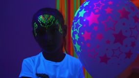 Κορίτσι με το φθορισμού aquagrim στο πρόσωπο δερμάτων που καμμένος νέο στο σκοτάδι απόθεμα βίντεο