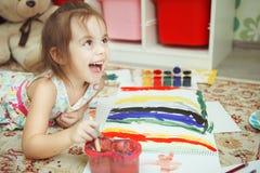 Κορίτσι με το χαμόγελο στο πρόσωπο και τη βούρτσα της υπό εξέταση Στοκ Εικόνες