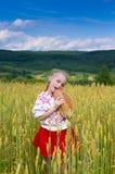 Κορίτσι με το ψωμί στον τομέα σίτου Στοκ Φωτογραφία
