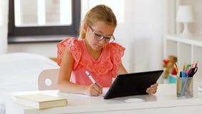 Κορίτσι με το PC ταμπλετών που γράφει στο σημειωματάριο στο σπίτι απόθεμα βίντεο