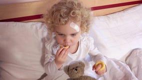 Κορίτσι μικρών παιδιών με την καλυμμένη πληγή στα επικεφαλής μπισκότα καλαμποκιού κατανάλωσής της που κάθεται στο κρεβάτι απόθεμα βίντεο
