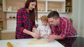 Κορίτσι μικρών παιδιών με τους γονείς της που κόβουν τα μπισκότα από τη ζύμη απόθεμα βίντεο