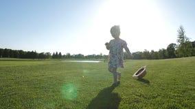 Κορίτσι μικρών παιδιών με το κάτω σύνδρομο που περπατά στη χλόη απόθεμα βίντεο