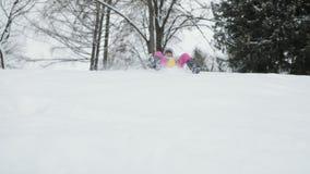 Κορίτσι μικρών παιδιών που πηγαίνει κάτω από ένα έλκηθρο σε έναν χιονώδη λόφο απόθεμα βίντεο