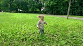 Κορίτσι μικρών παιδιών που τρέχει μέσω του λιβαδιού στο πάρκο Το ευτυχές παιδί έχει τη διασκέδαση υπαίθρια απόθεμα βίντεο