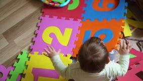Κορίτσι μικρών παιδιών ht στο efloor που παίζει στο σπίτι με το γρίφο χαλιών αφρού με τους αριθμούς, πρόωρη ανάπτυξη φιλμ μικρού μήκους