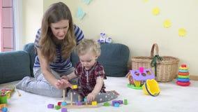 Κορίτσι μικρών παιδιών με τα ξύλινα ζωηρόχρωμα τούβλα τραβήγματος παιχνιδιού μητέρων της στους πόλους στο σπίτι φιλμ μικρού μήκους