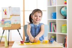 Κορίτσι μικρών παιδιών παιδάκι που δημιουργεί τα παιχνίδια από το playdough Στοκ φωτογραφία με δικαίωμα ελεύθερης χρήσης