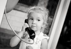 Κορίτσι μικρών παιδιών που μιλά με το τηλέφωνο πόλεων στοκ εικόνες