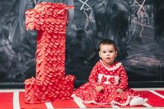 Κορίτσι μικρών παιδιών σε ένα κόκκινο φόρεμα σε μια άσπρη συνεδρίαση κύκλων κοντά σε έναν μεγάλο αριθμό ένας 1χρονο κορίτσι στα γ Στοκ Φωτογραφία