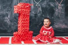 Κορίτσι μικρών παιδιών σε ένα κόκκινο φόρεμα σε μια άσπρη συνεδρίαση κύκλων κοντά σε έναν μεγάλο αριθμό ένας 1χρονο κορίτσι στα γ Στοκ εικόνες με δικαίωμα ελεύθερης χρήσης