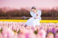 Κορίτσι μικρών παιδιών στο παιχνίδι κοστουμιών νεράιδων σε έναν τομέα λουλουδιών Στοκ εικόνα με δικαίωμα ελεύθερης χρήσης