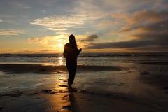 Κορίτσι μπροστά από το ηλιοβασίλεμα θάλασσας Στοκ Φωτογραφίες