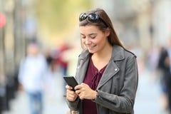 Κορίτσι μόδας που στέκεται χρησιμοποιώντας ένα έξυπνο τηλέφωνο στην οδό Στοκ φωτογραφία με δικαίωμα ελεύθερης χρήσης