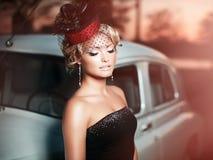 Κορίτσι μόδας στην αναδρομική τοποθέτηση ύφους κοντά στο παλαιό αυτοκίνητο Στοκ Εικόνες