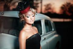 Κορίτσι μόδας στην αναδρομική τοποθέτηση ύφους κοντά στο παλαιό αυτοκίνητο Στοκ Φωτογραφίες