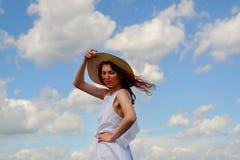 Κορίτσι μόδας στο άσπρα φόρεμα και το καπέλο, μπλε ουρανός και σύννεφα στο υπόβαθρο Στοκ Εικόνα