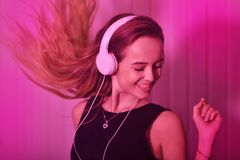 Κορίτσι μόδας χορού δροσερό αρκετά στα ακουστικά που ακούει τη μουσική πέρα από το ρόδινο υπόβαθρο Ενεργειακό πρότυπο με μακρυμάλ Στοκ εικόνες με δικαίωμα ελεύθερης χρήσης