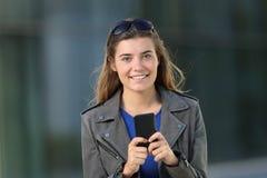 Κορίτσι μόδας χρησιμοποιώντας ένα τηλέφωνο και εξετάζοντας σας Στοκ Φωτογραφία