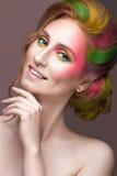 Κορίτσι μόδας με το χρωματισμένο πρόσωπο και τρίχα που χρωματίζεται Στοκ Εικόνα