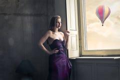 Κορίτσι μόδας που κοιτάζει από το παράθυρο Στοκ Εικόνες