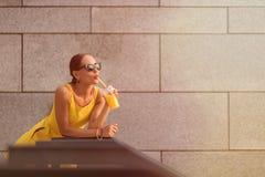 Κορίτσι μόδας που πίνει το πορτοκαλί κοκτέιλ Στοκ Εικόνες
