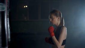 Κορίτσι, νέα γυναίκα που κάνει τον εγκιβωτισμό με μια punching τσάντα, που για μόνο - υπεράσπιση φιλμ μικρού μήκους