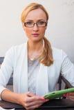 Κορίτσι ξανθών μαλλιών στο κοστούμι και γυαλιά που κάθονται στον πάγκο με το TA Στοκ Εικόνες