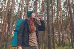 Κορίτσι οδοιπόρων που απολαμβάνει το νερό Ευτυχής τουρίστας γυναικών με το πόσιμο νερό σακιδίων πλάτης από το μπουκάλι στη φύση Στοκ Φωτογραφίες
